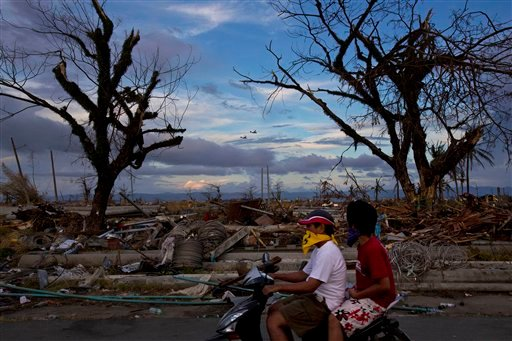 Typhoon Haiyan survivors pass by on a scooter as two U.S. Osprey aircraft fly over the ruins of Tacloban, central Philippines on Wednesday, Nov. 13, 2013. (AP Photo/David Guttenfelder)