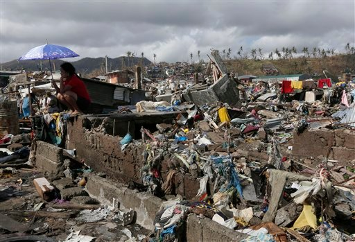 A survivor sits among debris in the typhoon ravaged city of Tacloban, Leyte province, central Philippines on Wednesday, Nov. 13, 2013. (AP Photo/Vincent Yu)