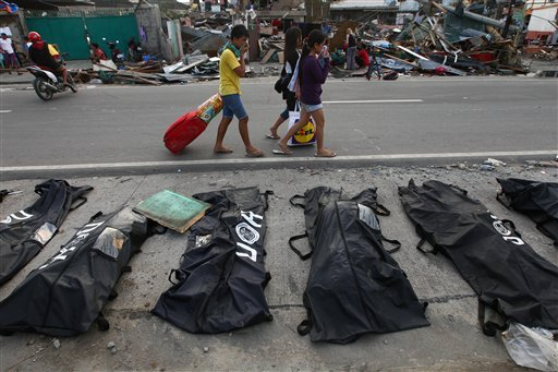 People cover their noses from the stench of dead bodies in an area affected by Typhoon Haiyan in Tacloban, Philippines, Wednesday, Nov. 13, 2013. (AP Photo/Dita Alangkara)