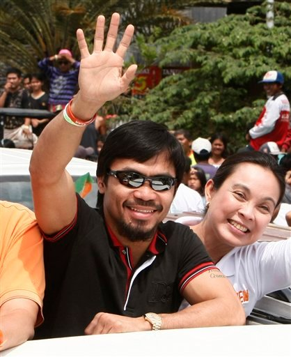 In this March 26, 2010 file photo, Filipino boxing great Manny Pacquiao waves from a vehicle at his election campaign during a motorcade sortie from General Santos city to Sarangani province in southern Philippines.