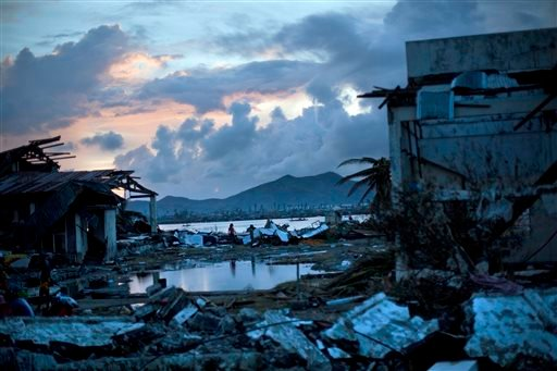 Typhoon Haiyan survivors walk through the ruins of their neighborhood on the outskirts of Tacloban, central Philippines on Wednesday, Nov. 13, 2013. (AP)