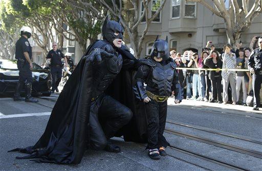 Miles Scott, dressed as Batkid, right, walks with Batman before saving a damsel in distress in San Francisco, Friday, Nov. 15, 2013.