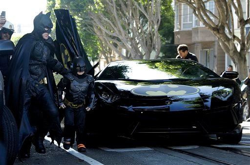 Miles Scott, dressed as Batkid, second from left, exits the Batmobile with Batman to save a damsel in distress in San Francisco, Friday, Nov. 15, 2013.