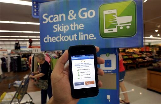 In this Sept. 19, 2013 photo, a Wal-Mart representative demonstrates a Scan & Go mobile application on a smartphone at a Wal-Mart store in San Jose, Calif.
