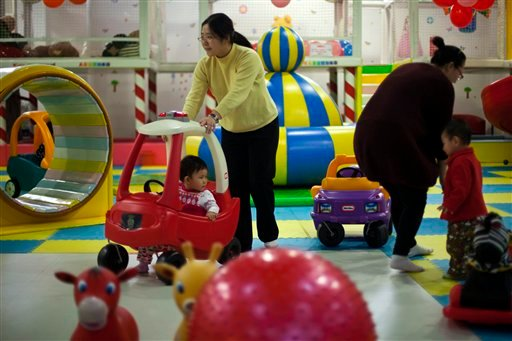 In this Jan. 10, 2013 photo, parents play with their children at a kid's play area in a shopping mall in Beijing. China will loosen its decades-old one-child policy and abolish a much-criticized labor camp system, its ruling Communist Party said Nov. 15.