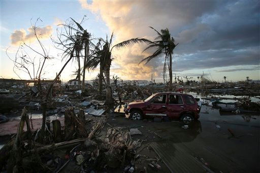As the sun sets, it lights the sky over the area devastated by Typhoon Haiyan, in Tacloban, central Philippines, Friday, Nov. 15, 2013.