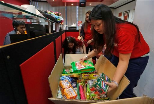 In this Wednesday, Nov. 13, 2013 photo, Filipino staff members at an express company in a Hong Kong shopping mall pack boxes of donations of relief goods from overseas workers to be shipped to survivors of Typhoon Haiyan. (AP)