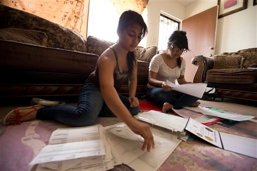In this Wednesday, Aug. 15, 2012 file photo, Itzel Guillen, left, sorts out some of the documents she needs to apply for a work permit along with Lucero Maganda, right, at her home in San Diego, Ca.