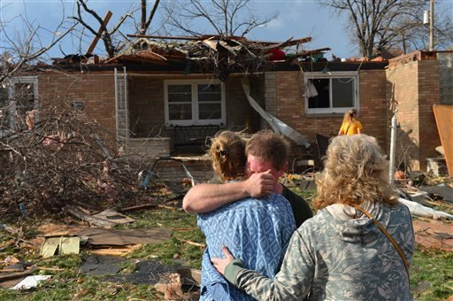 Ray Baughman embraces family shortly after his home was destroyed by a tornado that left a path of devastation through the north end of Pekin, Il., Sunday, Nov. 17, 2013.