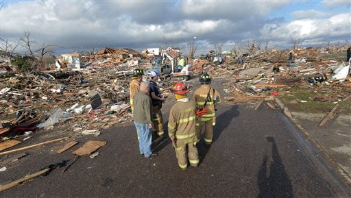 Washington, Ill., firefighters stand in the middle of Devonshire Street on the North side of Washington, Ill., after a tornado leveled at least fifty homes, Sunday, Nov. 17, 2013.