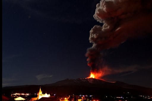 In this photo taken on Saturday, Nov. 16, 2013, Mt. Etna, Europe's most active volcano, spews lava as smoke billows during an eruption as seen from Acireale, near the Sicilian town of Catania, Italy. (AP Photo/Carmelo Imbesi)