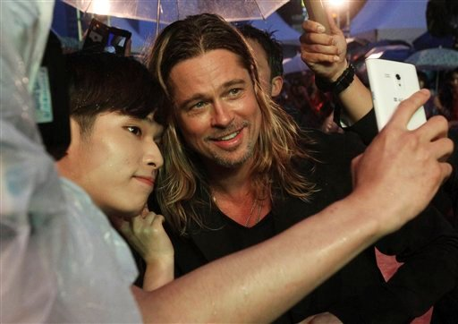 "In this Tuesday, June 11, 2013 file photo U.S. actor Brad Pitt poses for a photo with a fan upon arrival at the South Korea premiere of his latest film ""World War Z"" in Seoul."
