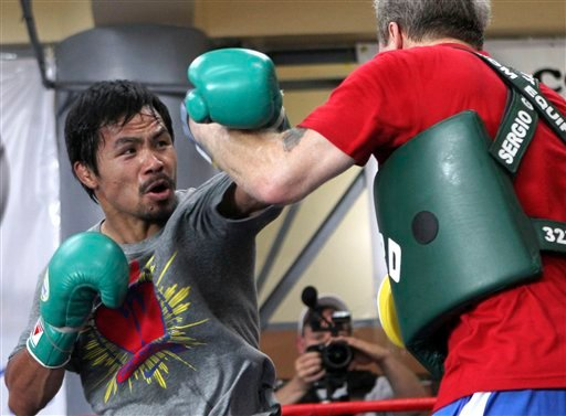 In this March 23, 2011 file photo, Filipino boxer Manny Pacquiao, left, trains with coach Freddie Roach in Baguio, northern Philippines.