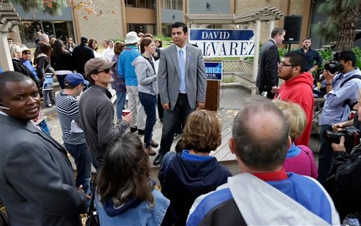David Alvarez, above center, a San Diego city councilman and Democratic candidate for mayor, looks on as he meets with supporters Tuesday, Nov. 19, 2013, in San Diego. (AP)