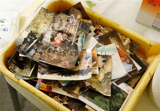 A tub full of photos is pictured at the Oklahoma School of Photography in Moore, Okla., Wednesday, Nov. 20, 2013, where Kristi Brummal and a team of about 50 volunteers are trying to clean, restore and reunite photos with their owners. (AP)