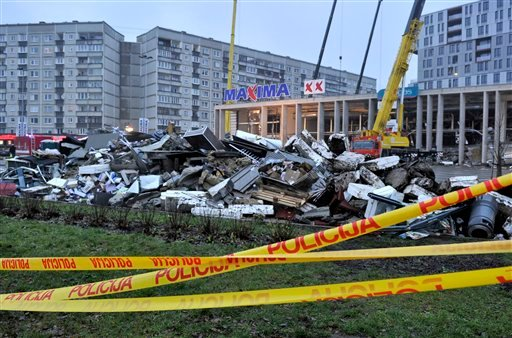 Debris, foreground,which was removed by rescue teams during a search for victims at the Maxima supermarket in Riga, Latvia, Friday, Nov. 22, 2013.
