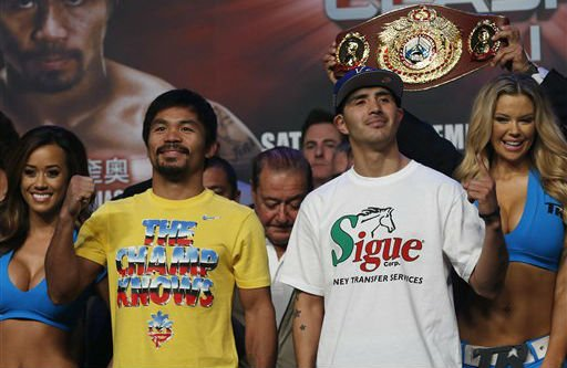 Filipino boxer Manny Pacquiao, left, and Brandon Rios of the United States pose for photos during the weigh-in for their welterweight fight at the Venetian Macao in Macau Saturday, Nov. 23, 2013.