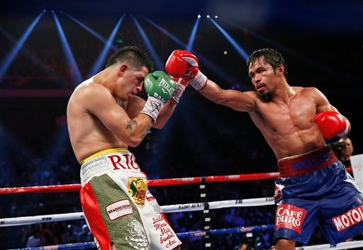Manny Pacquiao, from the Philippines, right, punches Brandon Rios of the United States during their WBO international welterweight title fight Sunday, Nov. 24, 2013, in Macau.