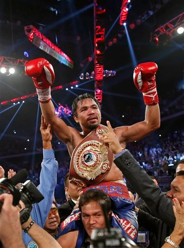 Manny Pacquiao from the Philippines wears the champion's belt after defeating Brandon Rios of the United States in their WBO international welterweight title fight Sunday, Nov. 24, 2013, in Macau.