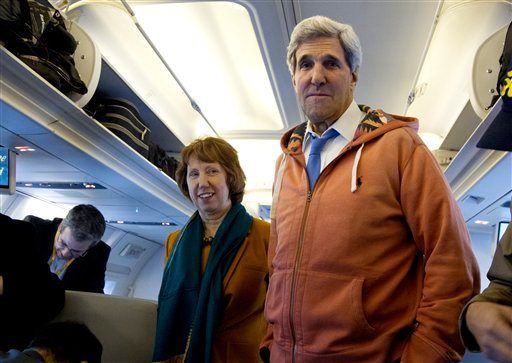 U.S. Secretary of State John Kerry, right, and EU foreign policy chief Catherine Ashton, left, visit the media seating area of Kerry's aircraft as it sits on the tarmac at Geneva International airport before leaving for London, Sunday, Nov. 24, 2013.