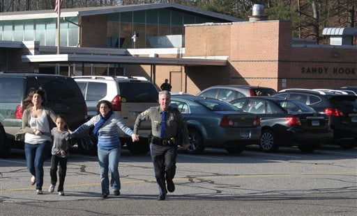 In this Friday, Dec. 14, 2012, file photo provided by the Newtown Bee, a police officer leads two women and a child from Sandy Hook Elementary School in Newtown, Conn., where a gunman opened fire, killing 26 people, including 20 children.