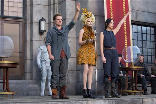 """This image released by Lionsgate shows Josh Hutcherson as Peeta Mellark, from left, Elizabeth Banks as Effie Trinket and Jennifer Lawrence as Katniss Everdeen in a scene from """"The Hunger Games: Catching Fire."""""""