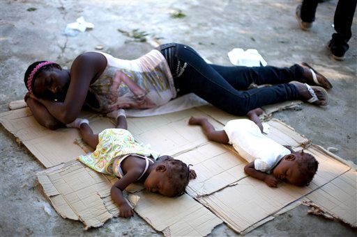 Marie Matte Mayan 26, sleeps on the floor with her twins, Maudeline and Maudena Pierre an a shelter after being deported by Dominican Republic authorities, in Croix-des-Bouquets, Haiti, Sunday Nov. 24, 2013.