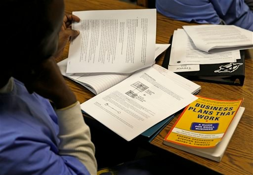 In this Thursday, Nov. 7, 2013 photo, an inmate looks over materials on a business model canvas during a session of The Last Mile at San Quentin State Prison in San Quentin, Calif.