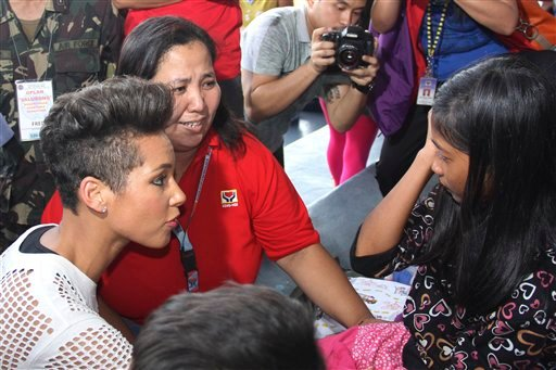 In this photo released by the Philippine Air Force, Grammy-winning singer Alicia Keys, left, talks to a typhoon survivor as she visits the Villamor Air Base in suburban Pasay, south of Manila, Philippines, Monday Nov. 25, 2013.