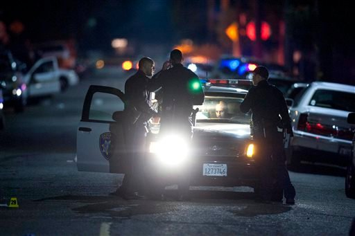 In this Monday Nov. 25, 2013 photo, Oakland police officers confer and gather evidence at the scene of a multiple shooting at the intersection of 96th Avenue and Olive Street in Oakland, Calif.