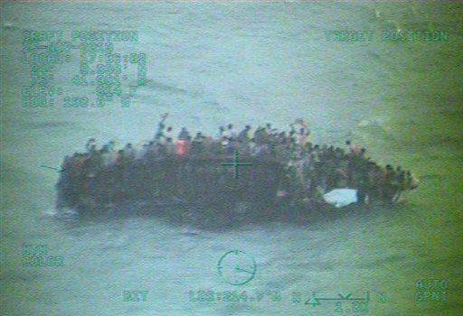 This image taken from video made available by the U.S. Coast Guard shows a group of Haitian migrants sitting on the hull of a capsized sailboat near Staniel Cay, Bahamas, Tuesday, Nov. 26, 2013. (AP)