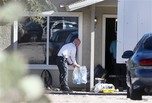 Tucson Police Department investigators and evidence technicians investigate the scene at a home where two people were arrested Tuesday, Nov. 26, 2013. (AP Photo/Arizona Daily Star, Mike Christy)