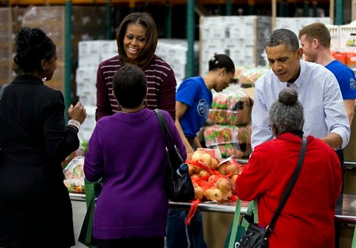 President Barack Obama, right, and first lady Michelle Obama participate in a Thanksgiving service project by handing out food at the Capital Area Food Bank on Wednesday, Nov. 27, 2013 in Washington. (AP Photo/ Evan Vucci)