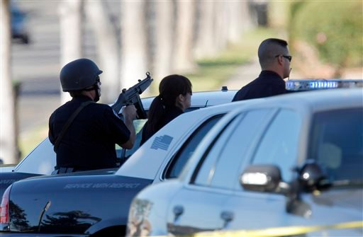 Inglewood police officers take up positions outside a residence, Wednesday, Nov. 27, 2013, in Inglewood, Calif. (AP Photo/Nick Ut)