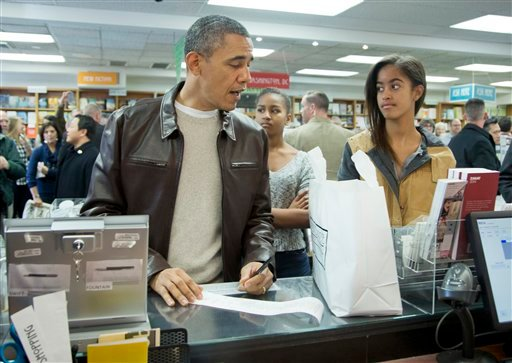 President Barack Obama, with daughters Sasha, center, and Malia, pays for his purchase the the local bookstore Politics and Prose in northwest Washington, Saturday, Nov. 30, 2013. (AP Photo/Manuel Balce Ceneta)