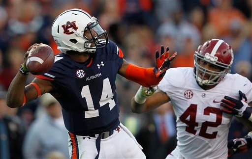 Auburn quarterback Nick Marshall (14) throws a pass as Alabama linebacker Adrian Hubbard (42) pressures during the first half of an NCAA college football game in Auburn, Ala., Saturday, Nov. 30, 2013. (AP Photo/Butch Dill)