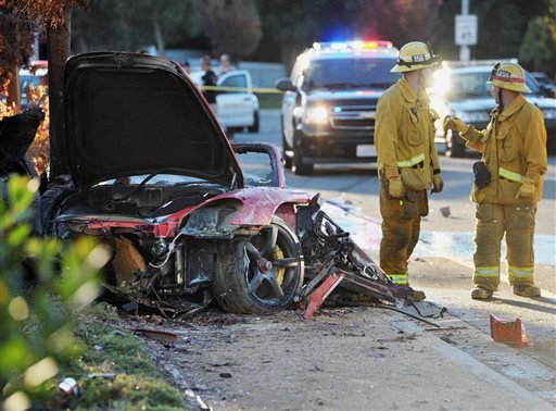 Sheriff's deputies work near the wreckage of a Porsche that crashed into a light pole on Hercules Street near Kelly Johnson Parkway in Valencia, Calif., on Saturday, Nov. 30, 2013.