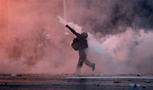 An anti-government protester throws back a tear gas canister fired by riot police in Bangkok, Sunday, Dec. 1, 2013.