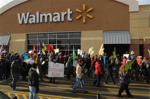 Protestors stream past the entrance to a Walmart store on Universty Avenue in St. Paul, Minn. on Black Friday, Nov. 29, 2013.