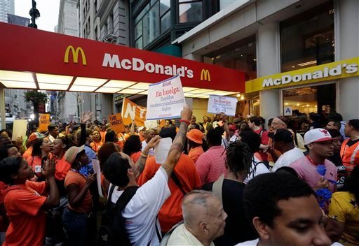 FILE - In this Thursday, Aug. 29, 2013, file photo, protesting fast food workers demonstrate outside a McDonald's restaurant on New York's Fifth Avenue, in New York. (AP)