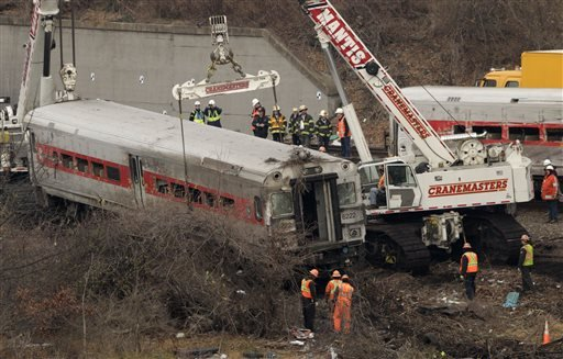Cranes salvage the last car from from a train derailment in the Bronx section of New York, Monday, Dec. 2, 2013.