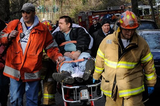 In this photo taken on Sunday, Dec. 1, 2013, Metro North Railroad engineer William Rockefeller is wheeled on a stretcher away from the area where the commuter train he was operating derailed in the Bronx borough of New York. (AP)