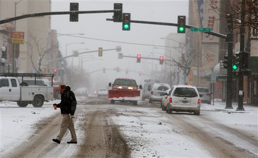 Cars and pedestrians creep along slick, snow-covered streets on Tuesday morning, Dec. 3, 2013 in downtown Casper, Wyo. (AP)