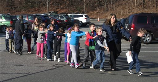 In this photo provided by the Newtown Bee, Connecticut State Police lead a line of children from the Sandy Hook Elementary School in Newtown, Conn. on Friday, Dec. 14, 2012 after a shooting at the school.(AP Photo/Newtown Bee, Shannon Hicks, File)
