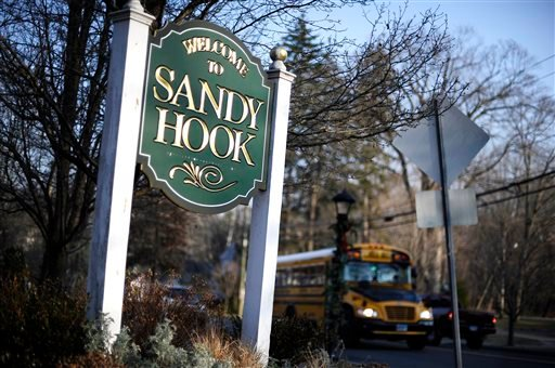 A bus drives past a sign reading Welcome to Sandy Hook, Wednesday, Dec. 4, 2013, in Newtown, Conn. (AP)