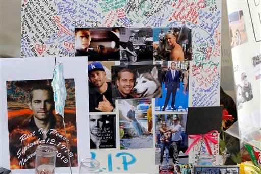 Photos and messages are seen at a roadside memorial at the site of the auto crash that took the life of actor Paul Walker and another man, in the small community of Valencia, Calif., Monday, Dec. 2, 2013.(AP Photo/Nick Ut)