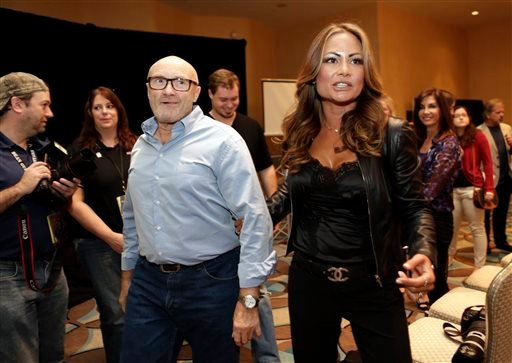 British musician Phil Collins, left, and Orianne Collins walk among the guests after his presentation of his Little Dreams Foundation, Wednesday, Dec. 4, 2013, in Miami Beach, Fla.