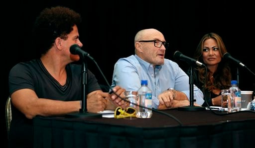 British musician Phil Collins, center, talks to guests about his Little Dreams Foundation, as Orianne Collins, right, and neo-pop artist Romero Britto, left, listen, Wednesday, Dec. 4, 2013, in Miami Beach, Fla.