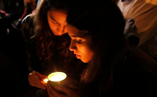People light a candle for former president Nelson Mandela on hearing of his death outside his home in Johannesburg, South Africa, Thursday, Dec. 5, 2013. (AP Photo/Denis Farrell)