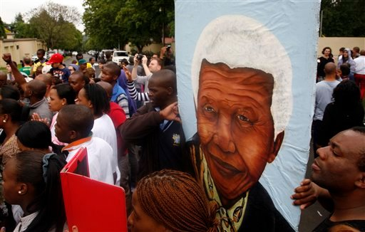 A group of mourners carrying a picture of South African leader Nelson Mandela, sing and dance outside his Johannesburg home, Friday, Dec. 6, 2013, after the freedom fighter passed away Thursday night after a long illness. (AP Photo/Themba Hadebe)